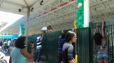 Jovem recebe ajuda para pular o portão do colégio Sigma, na Asa Sul